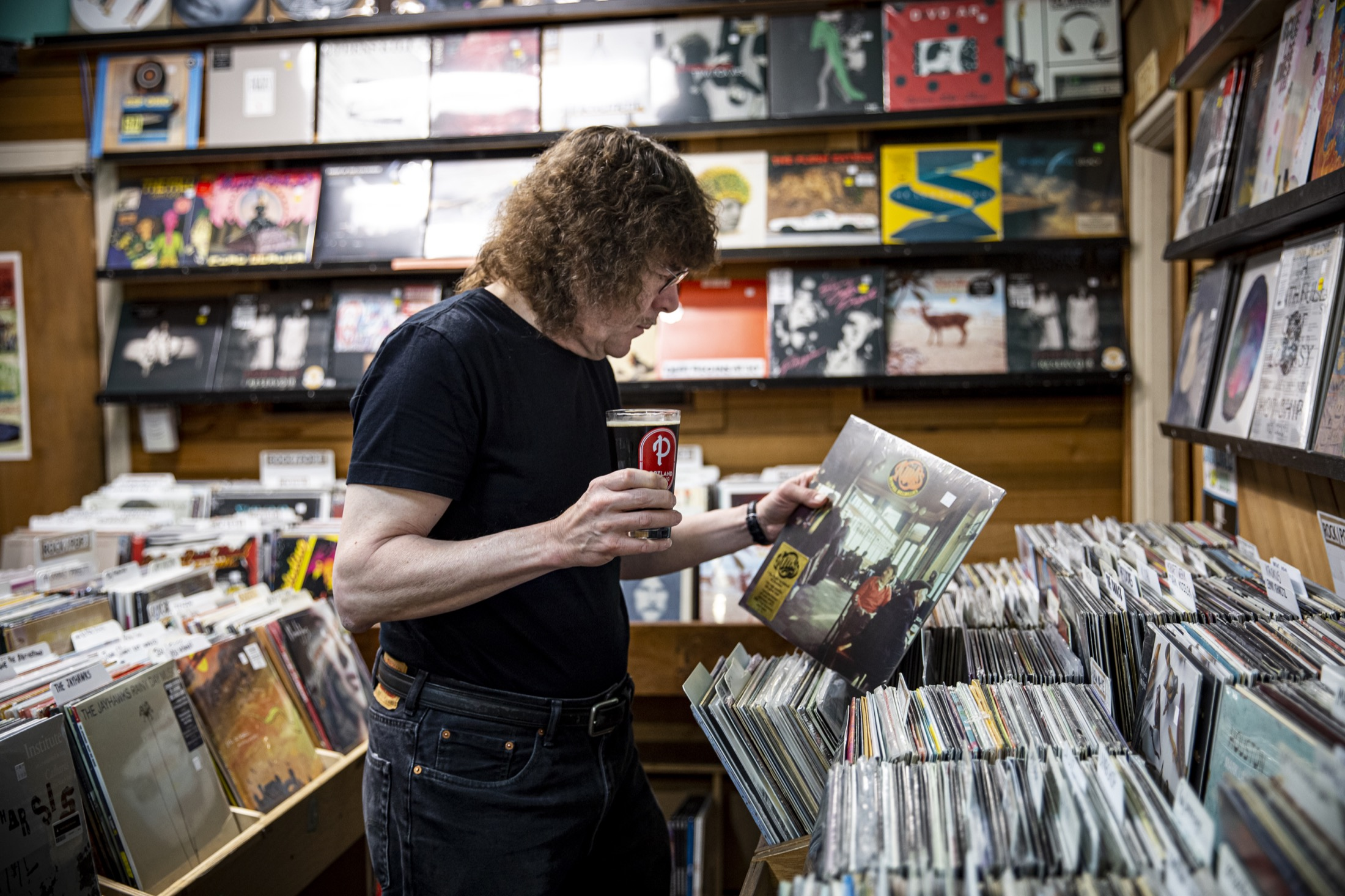 Terry Currier, owner of Music Millennium searching for some vinyl records with a Portland Brewing In The Groove Black Vinyl Lager. (image courtesy of Portland Brewing Co.)