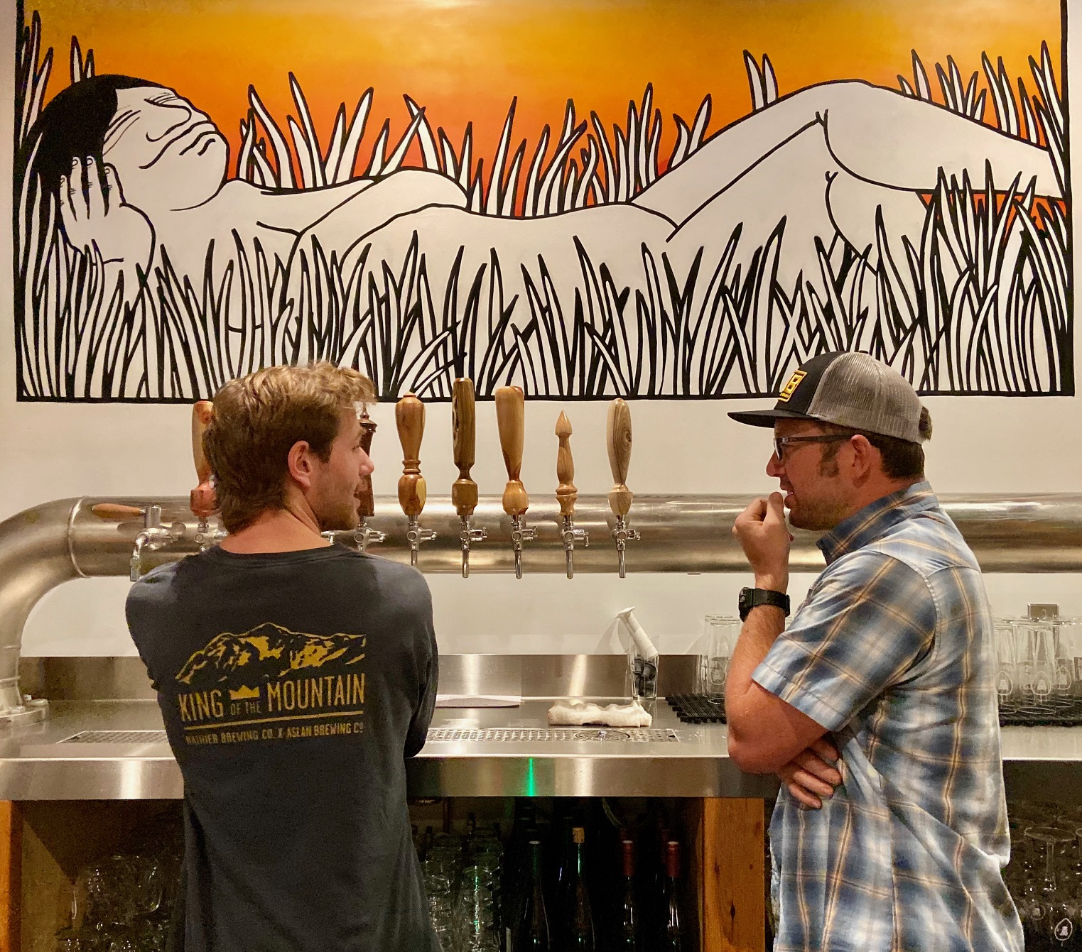 Co-Owner and CEO of Aslan Brewing, Jack Lamb pouring a beer while talking to Christian Ettinger from Hopworks Urban Brewery while at Aslan Brewing Seattle.