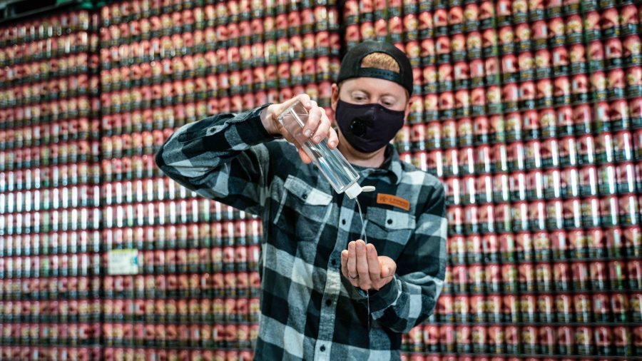 image of 2 Towns Ciderhouse CEO Lee Larsen using the Hand Sanitizer courtesy of 2 Towns Ciderhouse