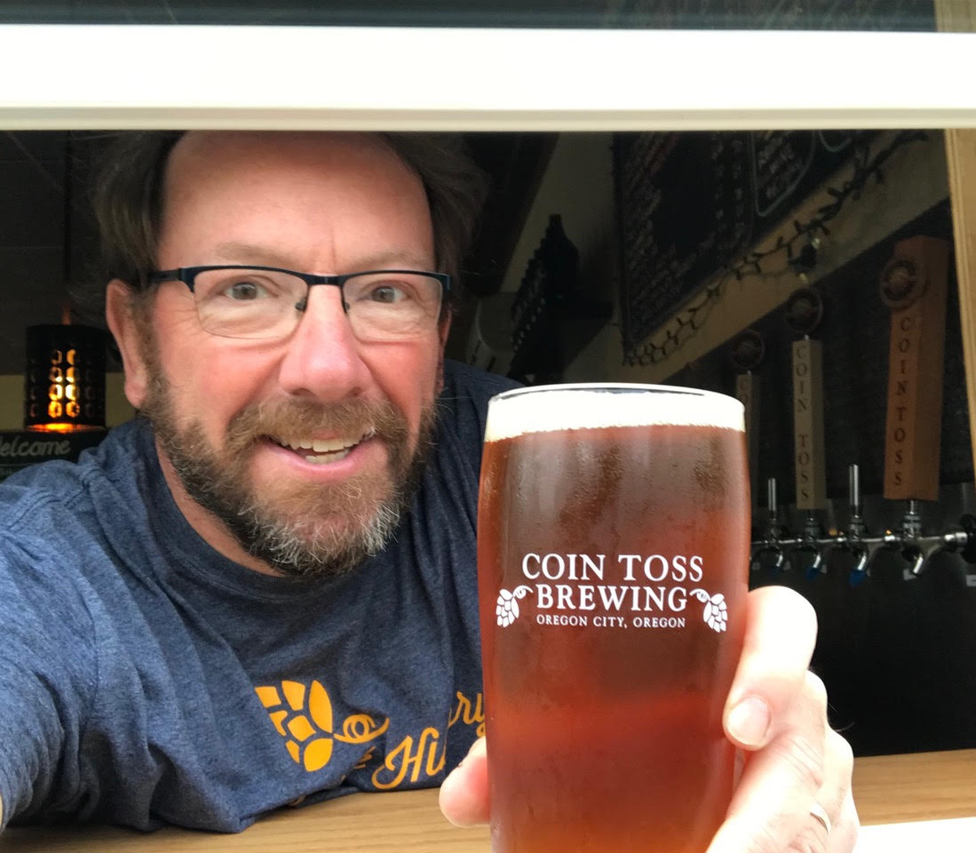 Tim Hohl serving a beer through the new beer window at Coin Toss Brewing in Oregon City, Oregon. (image courtesy of Coin Toss Brewing)