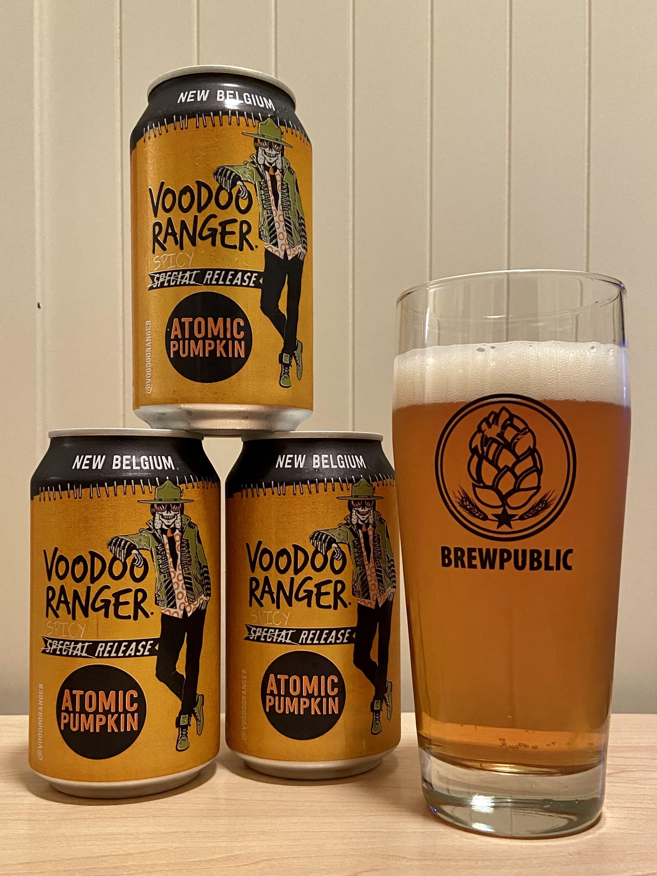 Cans of New Belgium Voodoo Ranger Atomic Pumpkin Ale served in a BREWPUBLIC glass.