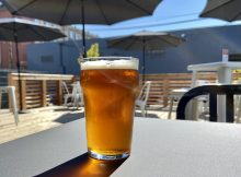The IPA from Hammer & Stitch Brewing with a view of the outdoor deck.