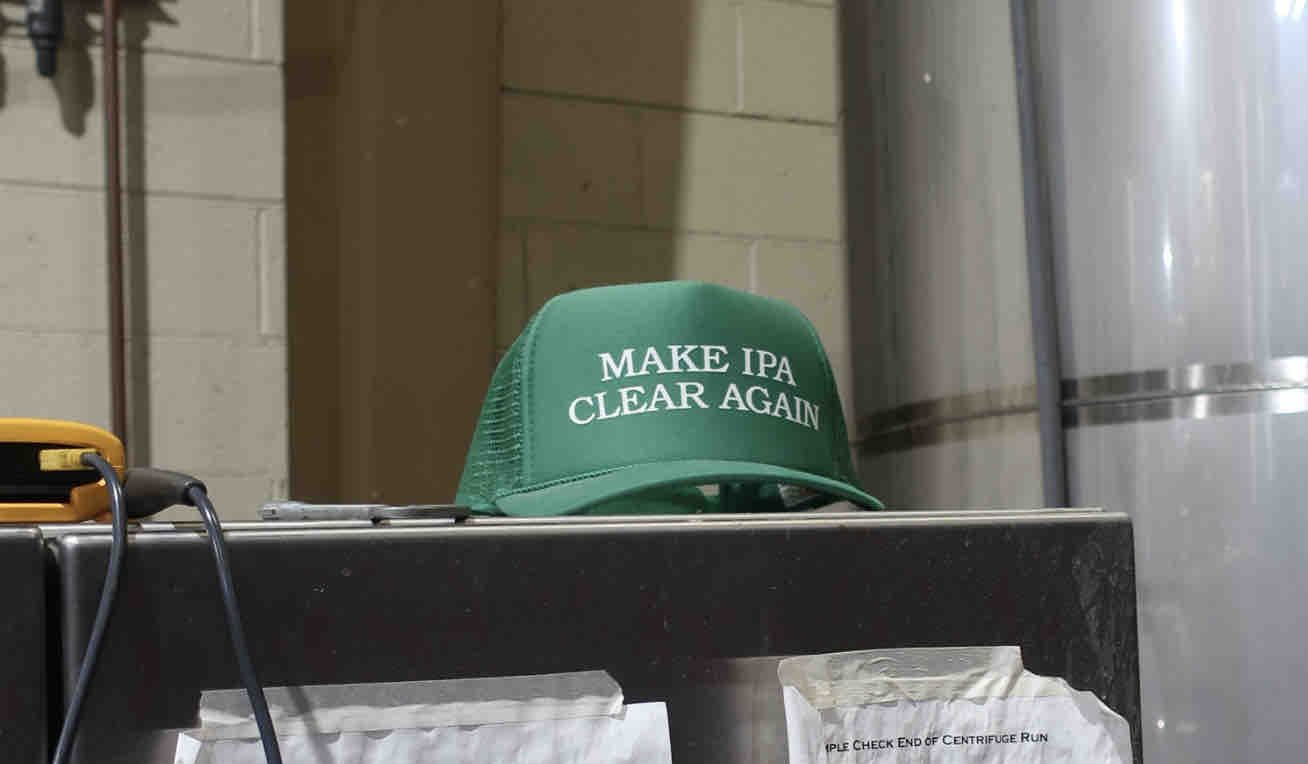 A Make IPA Clear Again hat that was gifted to Pelican Brewing from Comrade Brewing from Denver, Colorado