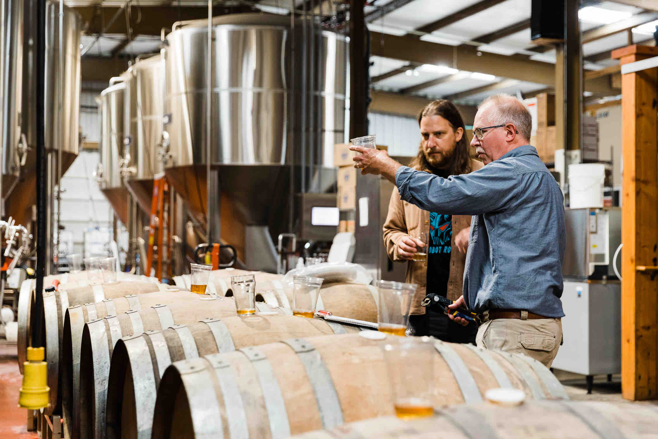 Ben Love and Darron Welch tasting through barrels to find the perfect blend for Bird-Day Volume II Tangerine Golden Ale Aged in Mezcal Barrels. (image courtesy of Pelican Brewing)