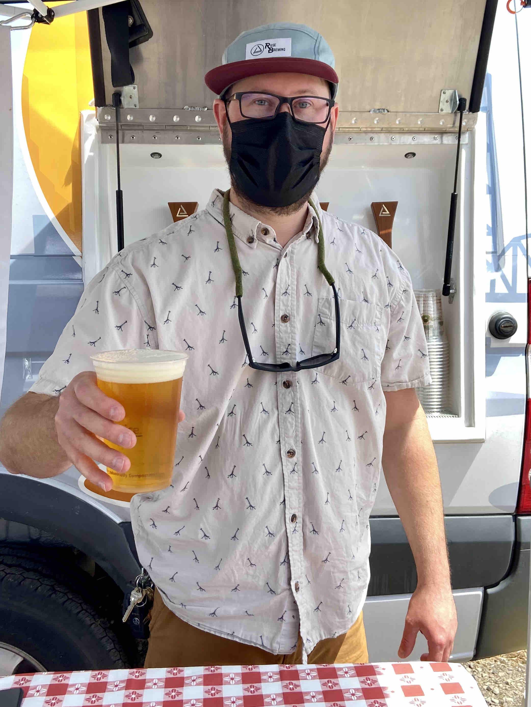 Devin Benware, co-owner of Ruse Brewing, serving beer at Brooklyn Garden.