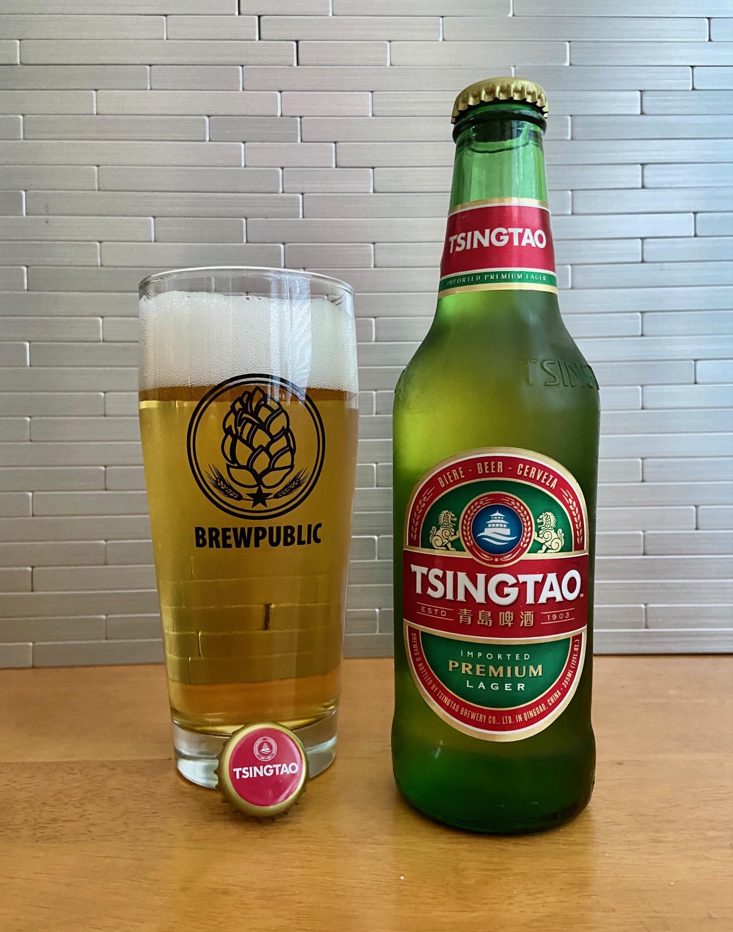 A 12oz bottle of Tsingtao poured into a Brewpublic Willi Becher glass.