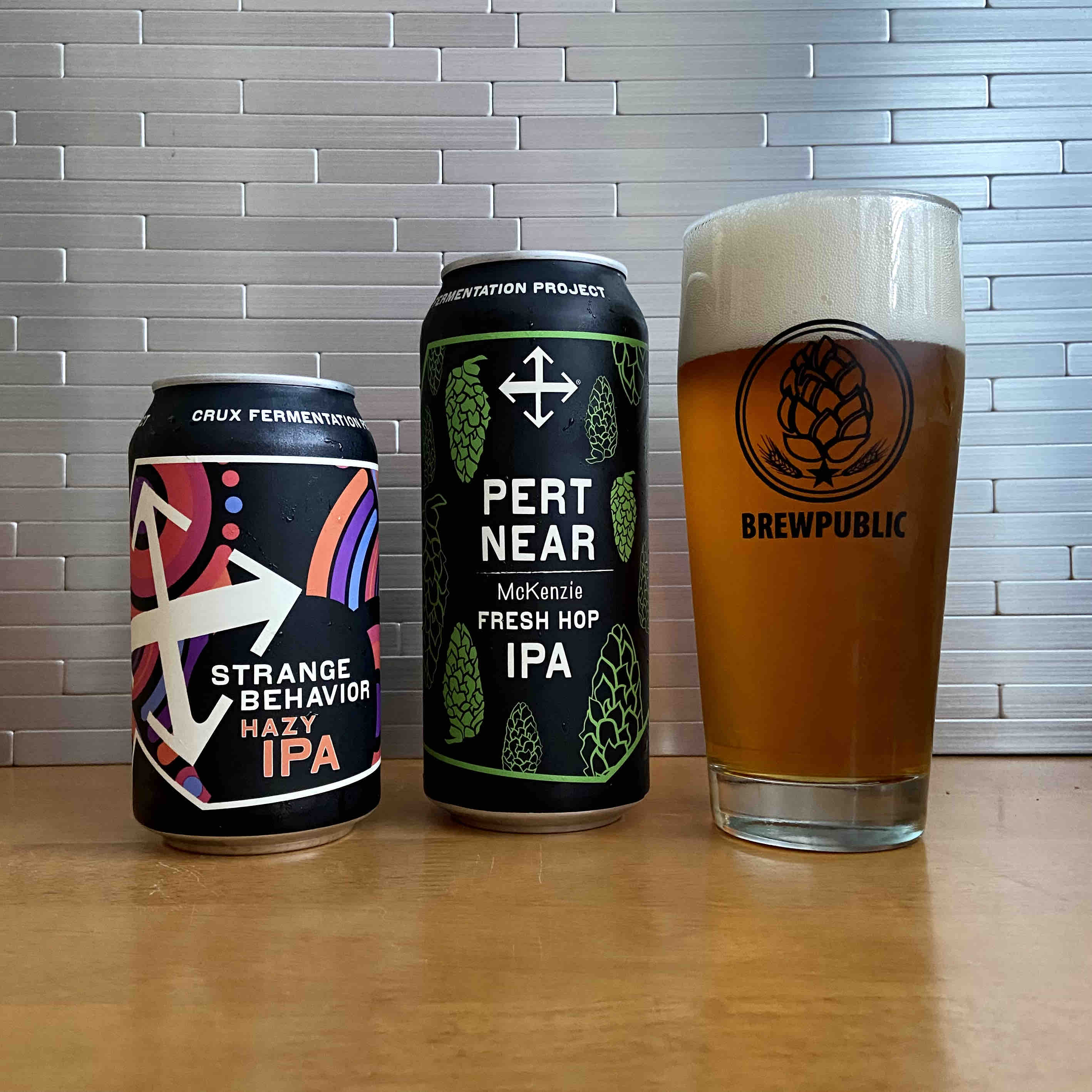 Strange Behavior Hazy IPA and a pour of a pint can of Pert Near Fresh Hip IPA from Crux Fermentation Project.